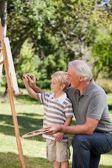 Feliz abuelo y su nieto pintando en el jardín