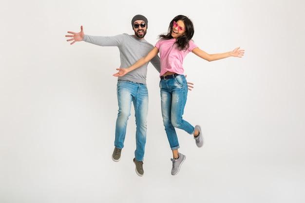 Feliz activo elegante hombre y mujer saltando juntos aislados