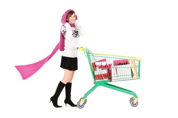 Feliz adolescente con carrito de compras sobre blanco