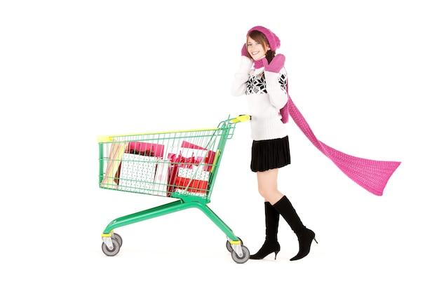 Feliz adolescente con carrito de compras sobre pared blanca