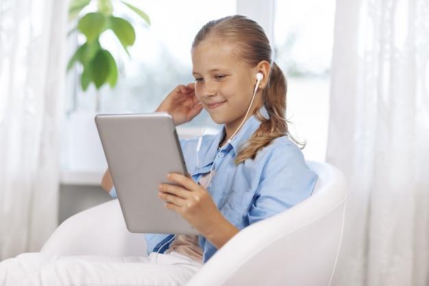 Feliz adolescente con ojos azules en una habitación luminosa, se sienta con una tableta y se comunica mediante una videollamada.