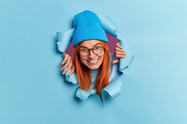 Feliz adolescente rompe a través de la pared de papel se divierte se ve con alegría viste sombrero azul gafas sonríe toothily