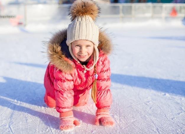 Feliz adorable niña sentada sobre hielo con patines después de la caída
