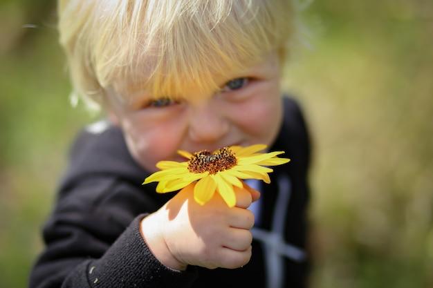 Feliz adorable niño australiano rubio sosteniendo una flor amarilla