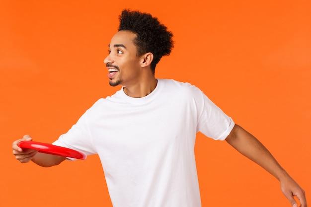 Feliz, alegre y carismático hombre afroamericano jugando con amigos, tirando frisbee rojo a la izquierda y sonriendo, pasando tiempo al aire libre en el parque, haciendo un picnic, vacaciones sobre la pared naranja