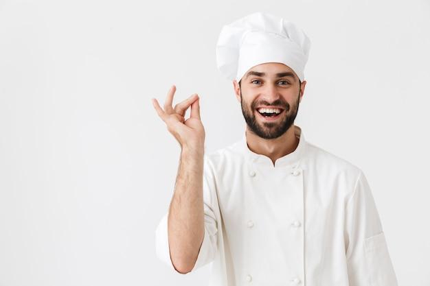 Feliz, alegre, contento, joven, chef, posar, en, uniforme, gesticular.