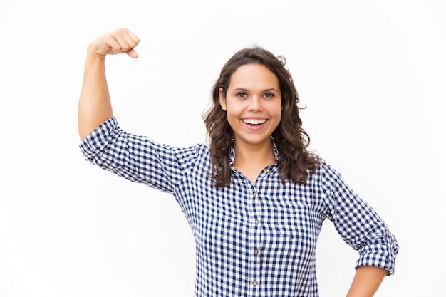 Feliz alegre feminista flexionando y mostrando bíceps