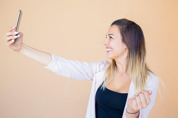 Feliz alegre hermosa dama tomando foto de sí misma