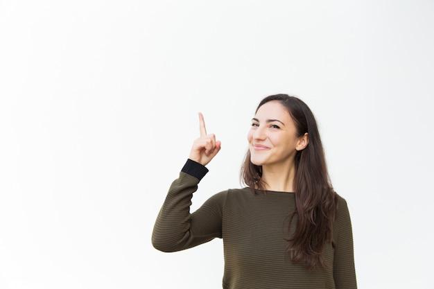 Feliz alegre hermosa mujer apuntando el dedo hacia arriba