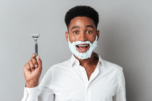 Feliz alegre hombre africano con cara en espuma de afeitar