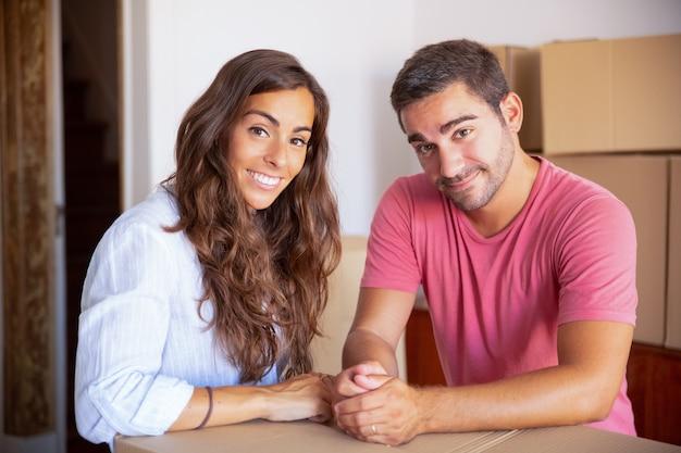 Feliz alegre hombre y mujer disfrutando de mudarse a casa nueva, de pie en el interior, apoyado en caja de cartón,