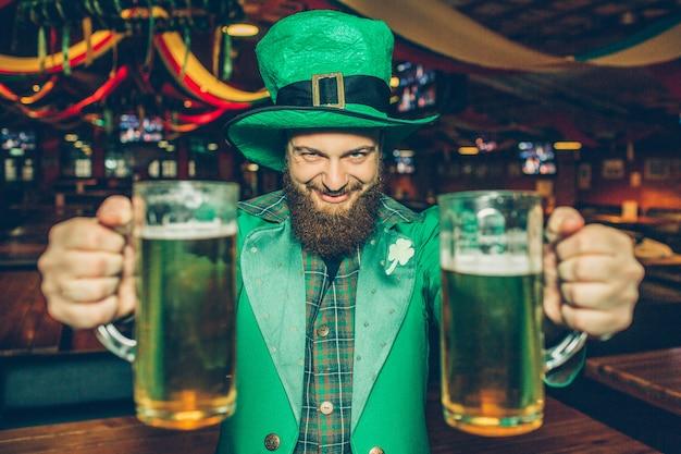 Feliz y alegre joven en traje de san patricio en pub solo. sostiene dos jarras de cerveza y mira.