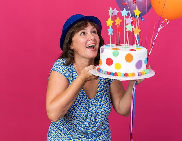 Feliz y alegre mujer de mediana edad con sombrero de fiesta con globos de colores sosteniendo pastel de cumpleaños mirando hacia arriba sonriendo ampliamente celebrando la fiesta de cumpleaños de pie sobre la pared rosa