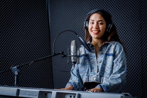 Feliz alegre muy sonriente de joven vocalista asiática con auriculares grabando una canción frente al micrófono y tocando el teclado durante el ensayo de su banda en un estudio profesional