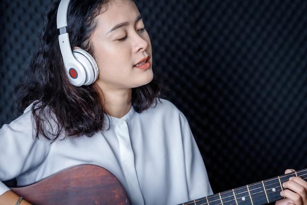 Feliz alegre muy sonriente retrato de una joven mujer asiática vocalista con auriculares con una guitarra grabando una canción frente al micrófono en un estudio profesional