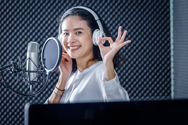 Feliz alegre muy sonriente de retrato de joven vocalista asiática con auriculares grabando una canción frente al micrófono en un estudio profesional