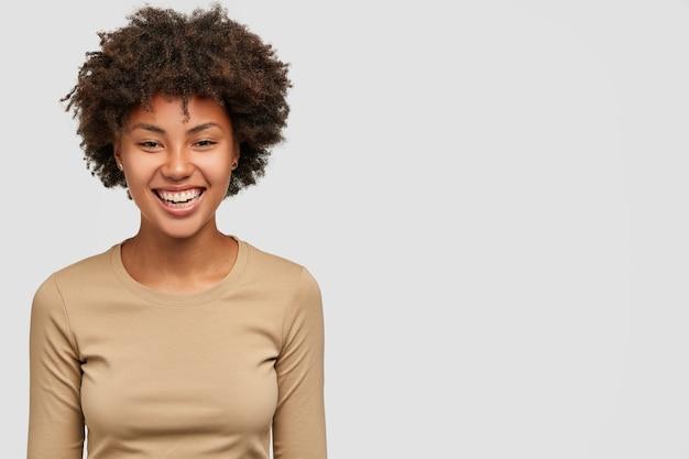 Feliz alegre niña de piel oscura sonríe suavemente