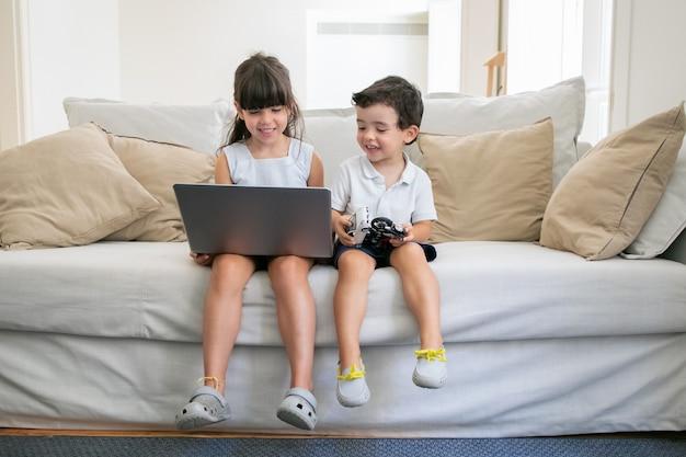 Feliz alegre niño y niña sentados en el sofá en casa, usando la computadora portátil, viendo videos, películas de dibujos animados o películas divertidas.