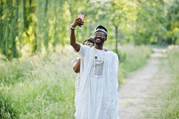 Feliz alegre pareja de africanos negros enamorados haciendo selfie en su teléfono