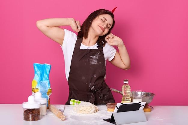 Feliz ama de casa o panadero estirando las manos después de un día cansado en la cocina