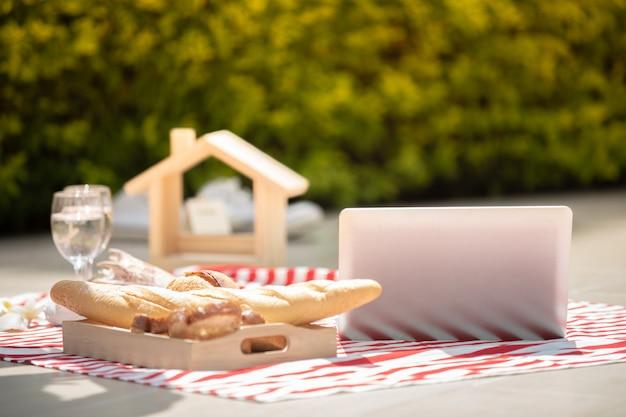 Feliz amante de las parejas románticas hablando y bebiendo vino mientras hacen un picnic en casa