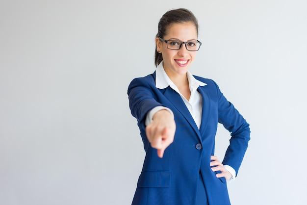 Feliz ambicioso joven dama de negocios apuntando con el dedo y de pie