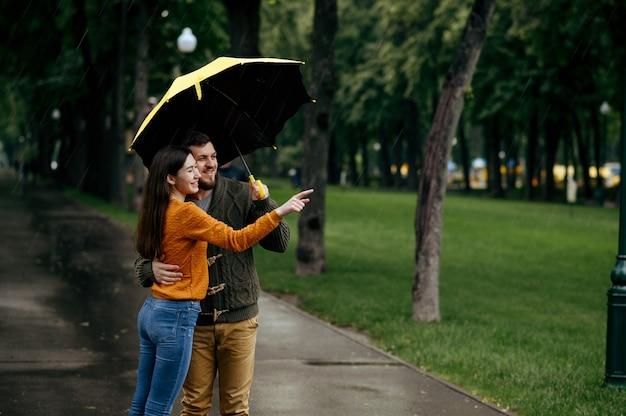 Feliz amor pareja ocios en el parque, día lluvioso de verano. el hombre y la mujer están parados bajo el paraguas bajo la lluvia, cita romántica en el sendero, clima húmedo en el callejón