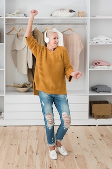 Feliz anciana bailando mientras escucha música en los auriculares