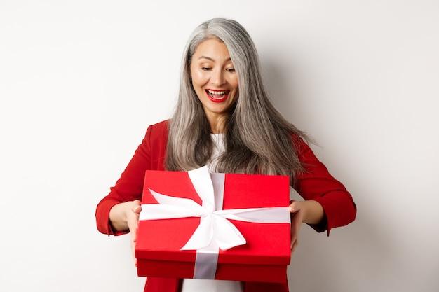 Feliz anciana con canas, recibir presente, mirando la caja de regalo roja y sonriendo sorprendido, de pie sobre fondo blanco.