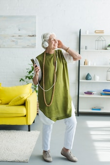 Feliz anciana disfrutando de la música en auriculares en casa