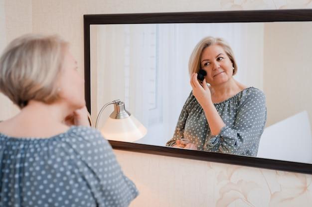 Feliz anciana de mediana edad preñez y ajusta su cabello frente al espejo del tocador