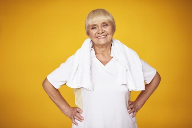 Feliz anciana orgullosa después de la toalla de entrenamiento en el cuello