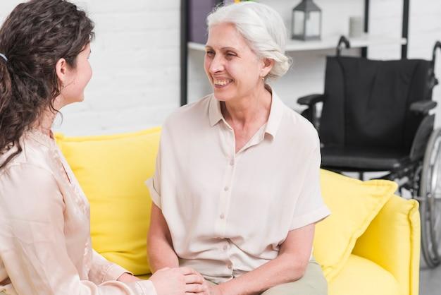 Feliz anciana con su hija sentada en el sofá en casa