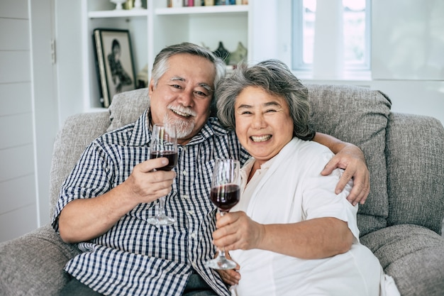 Feliz anciana y su marido bebiendo vino y felicidad
