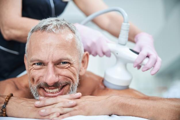 Feliz anciano acostado boca abajo mientras el especialista en spa realiza un procedimiento de cavitación ultrasónica en su cuerpo