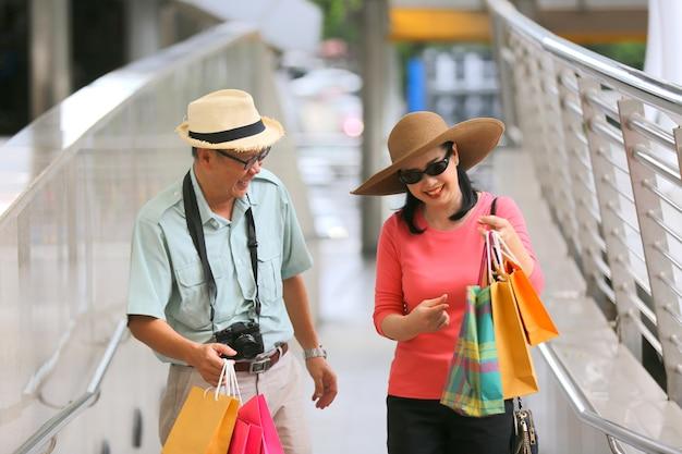 Feliz anciano y una mujer caminando en la calle en un día de verano. relajado pareja senior con sombreros ir de compras.
