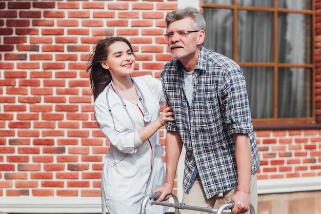Feliz anciano en silla de ruedas y amable enfermera al aire libre