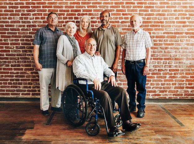 Feliz anciano en silla de ruedas con amigos