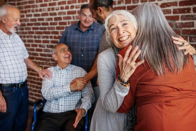 Feliz anciano en silla de ruedas hablando con amigos