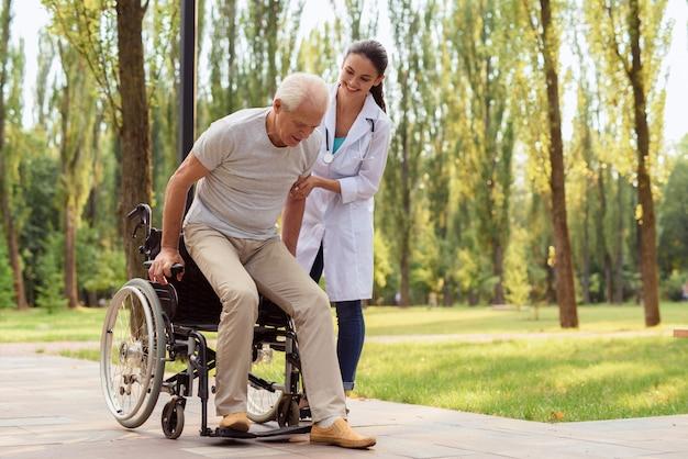 Feliz anciano trata de levantarse de la silla de ruedas e irse.