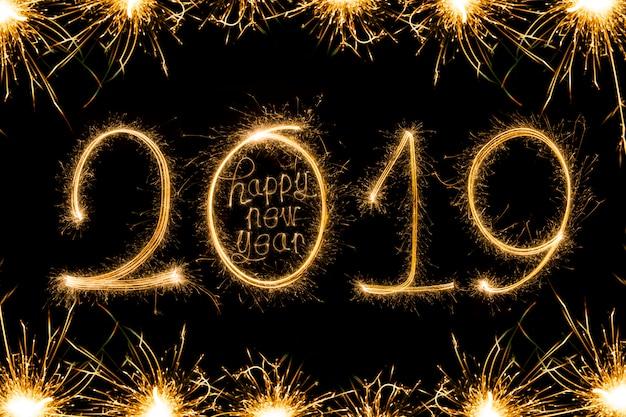 Feliz año nuevo 2018 texto escrito con fuegos artificiales sparkle aislados sobre fondo negro