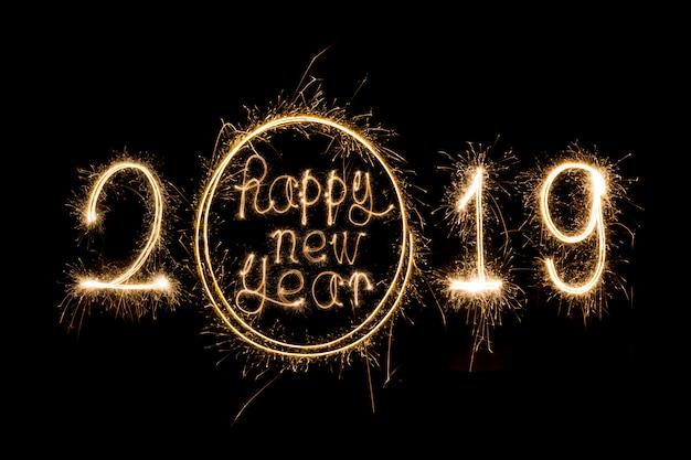 Feliz año nuevo 2019 escrito con fuegos artificiales sparkle