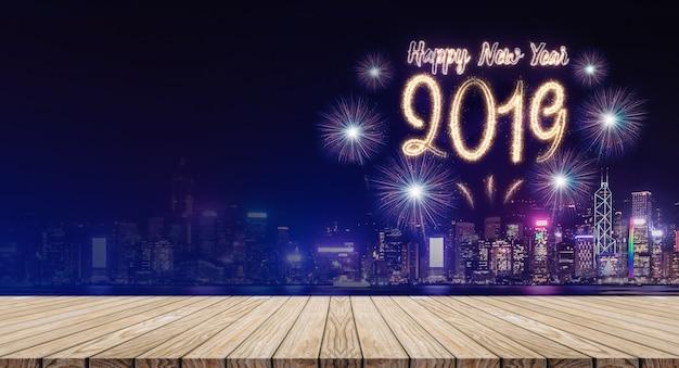 Feliz año nuevo 2019 fuegos artificiales sobre el paisaje urbano por la noche con mesa de tablones de madera vacía