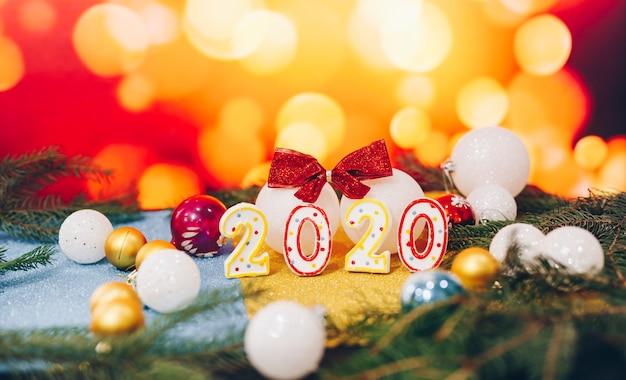 Feliz año nuevo 2020 con bolas de navidad en desenfoque de fondo