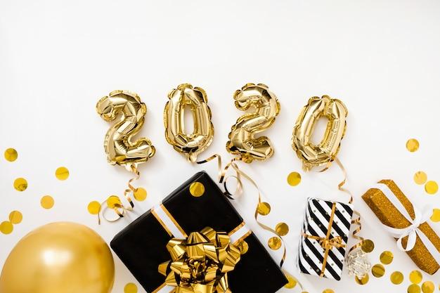 Feliz año nuevo 2020 celebración. lámina de oro globos número 2020 sobre fondo blanco con regalos