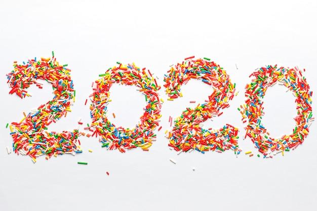 Feliz año nuevo 2020. forma de número colorido con chispitas de azúcar de arco iris brillante aislado en blanco