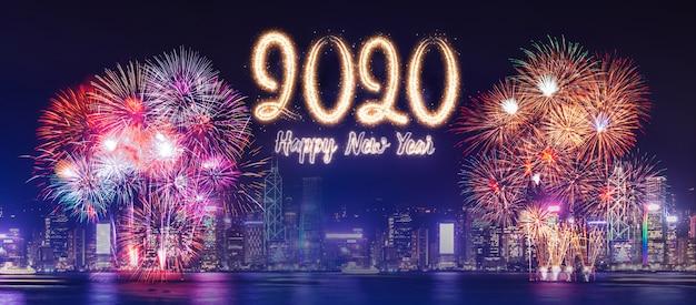 Feliz año nuevo 2020 fuegos artificiales sobre el edificio del paisaje urbano cerca del mar en la celebración nocturna