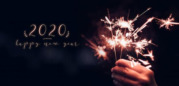 Feliz año nuevo 2020 con mano sosteniendo explosión de fuegos artificiales sparkler