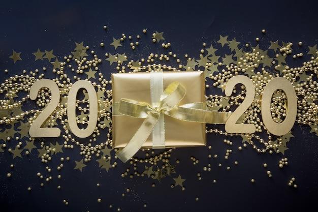 Feliz año nuevo 2020 tarjeta de felicitación. caja de regalo dorado de lujo con cinta dorada