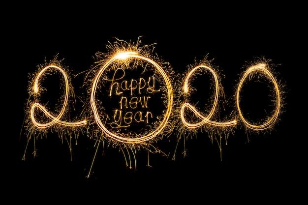 Feliz año nuevo 2020. texto creativo feliz año nuevo 2020 escrito bengalas brillantes